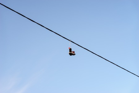 life change: Old pair of shoes hanging on telephone wire against blue sky, life change concept