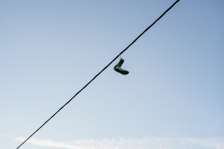 life change: Old pair of sneakers dangling on power line cable against blue sky, life change concept