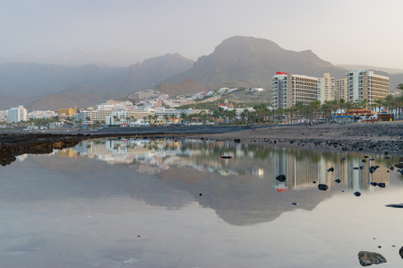 the americas: LAS AMERICAS, SPAIN - JANUARY 26, 2016: Picturesque coast of Las Americas resort town. On background mountains are engulfed by phenomenon known as the calima. Editorial