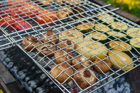 gridiron: Fresh mushrooms and vegetables grilling in gridiron, picnic in summer outdoors