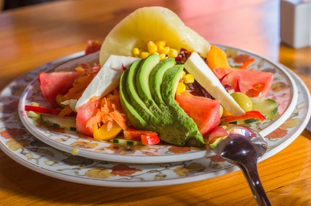goat peach: Fresh salad with avocado, tomatoes, goat cheese, olives, carrot, corn and pineapple Stock Photo