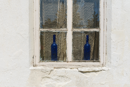 fishingnet: Decorative bottles from blue glass on a windowsill and fishing-net used as curtain, unusual home decor concept. View from outside