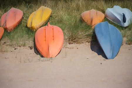 cabeza abajo: Al revés de colores kayak o canoa barcos establece en la playa de arena, el enfoque selectivo
