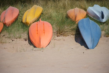 lays down: Upside down colorful kayak or canoe boats lays on sandy beach, selective focus Stock Photo