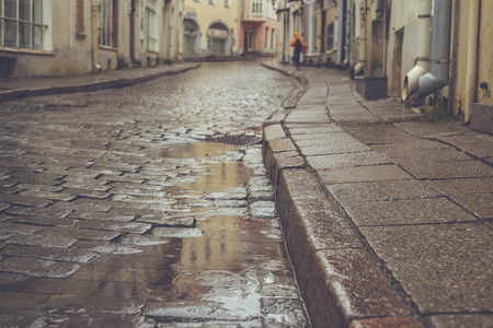 Old town pavement street on rainy day. Blurred and retro toned image, shallow depth of field