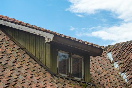 Mansard window in old tiled roof against blue sky