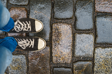 wet jeans: Teenage legs in sneakers and blue jeans standing on wet paving stones, top view, unusual perspective Stock Photo