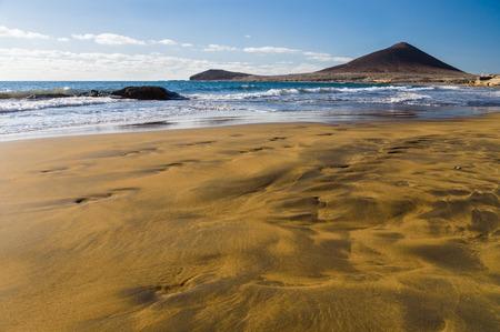 briny: Brown-yellow sand of Playa el Medano beach, Montana Roja mountain on background, Tenerife, Canary islands, Spain Stock Photo