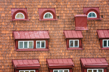 mansard: Old house tiled roof with many attic windows Stock Photo