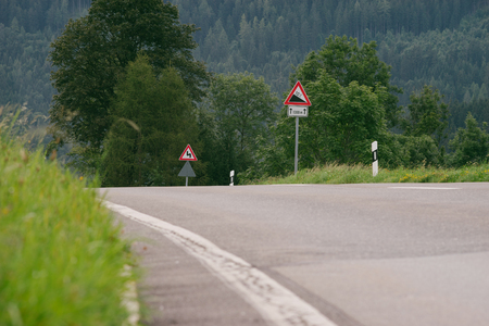 downgrade: Triangular roadsing in highland area warning a steep descent with a 10 percent slope