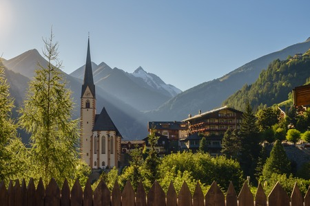 hohe tauern: St Vincent church against Grossglockner mountain and Hohe Tauern range sunlit by evening sun. Heiligenblut, Carinthia, Austria