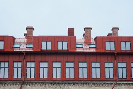 mansard: Top part of modern house with many windows, chimneys, rain-pipe and attic Stock Photo