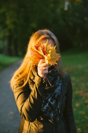 woman hiding: Young woman hiding face behind bunch of autumn fallen leaves