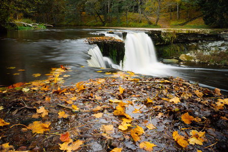 Keila-Joa waterfall by autumn. Fallen leaves on foreground. Long exposure image