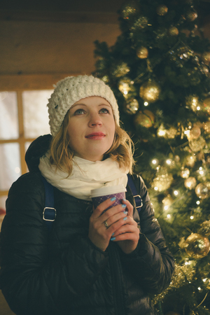 desires: Dreaming young woman with coffee near christmas tree. Accomplishment of desires concept