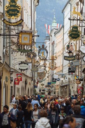 Salzbourg, Autriche - 21 août 2016: célèbre rue historique getreidegasse avec plusieurs panneaux publicitaires. Foule de passants et de commerçants.