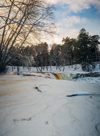 icefall: Partly frozen Keila-Joa waterfall by winter sunset. Long exposure vertorama. Harjumaa, Estonia Stock Photo