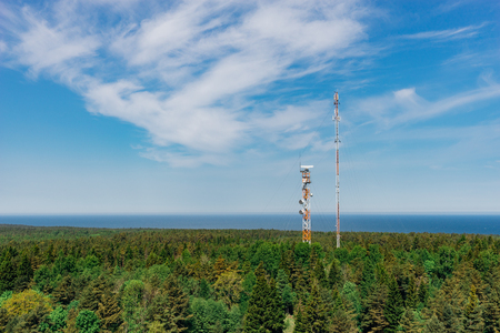 telephone poles: Telecommunication towers with TV antennas and satellite dish in forest, blue sky and sea on background