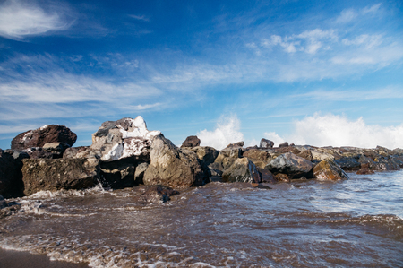 Powerful waves splashing over wave-breaker, scenic cloudscape on backdrop
