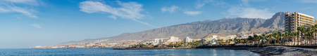 COSTA ADEJE, SPAIN - JANUARY 17 2016: Panoramic view on coastline of famous Tenerife resort. Mountains and El Teide volcano on background.