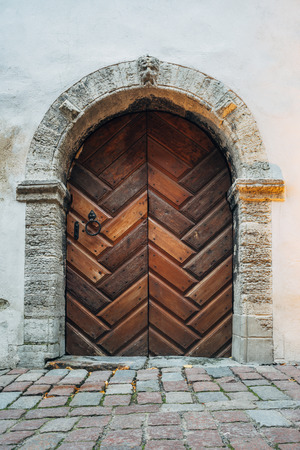 Medieval style wooden door with stone arch in old building on paved street