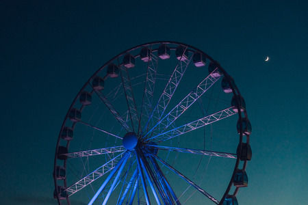 wheel spin: Inactive ferris wheel against dark evening sky with half moon