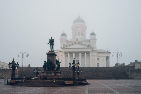 lutheran: Statue of emperor Alexander II and Helsinki Cathedral on background by foggy day, Finland Stock Photo