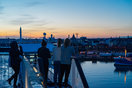 Unrecognizable tourists taking photo and enjoying Helsinki city sunset view from cruise ferry