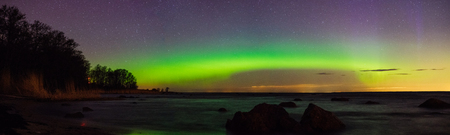 Starry sky and aurora borealis over stony sea shore, panoramic view Stock Photo