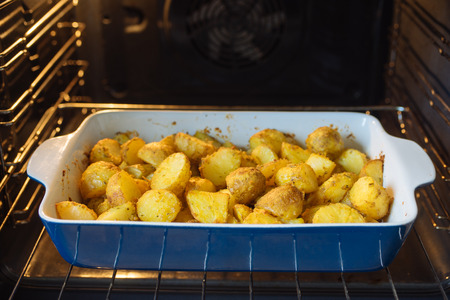 Baked potatoes with curcuma and other spices in roasting pan. Oven on background
