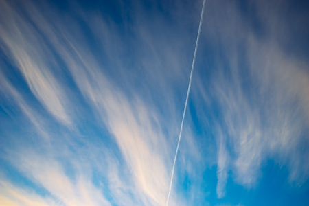 Trace of aircraft in morning sky with clouds. Vapor trail from airline fuel against beautiful cloudscape