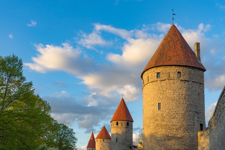 Medieval towers in a row against blue sky and clouds. Springtime evening in Tallinn, Estonia Stock Photo