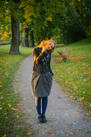 Young lady standing on path in autumnal park and look out through bunch of fallen leaves Stock Photo