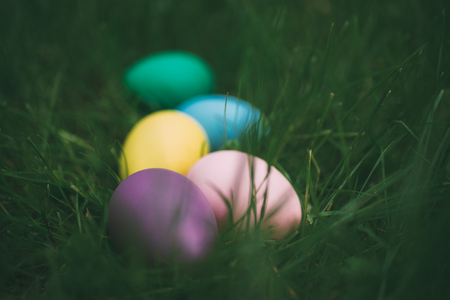 Colorful eggs on fresh springtime grass. Happy easter background. Shallow depth of field