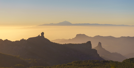 Silhouettes of Roque Nublo and Bentayga against sunset light. Pico de Teide on background. Gran Canaria, Canary islands, Spain