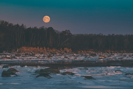 Scenic moonset over sea coast by winter morning