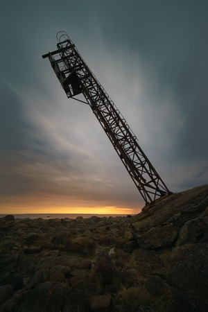 Falling tower against scenic sunrise clouds, long exposure