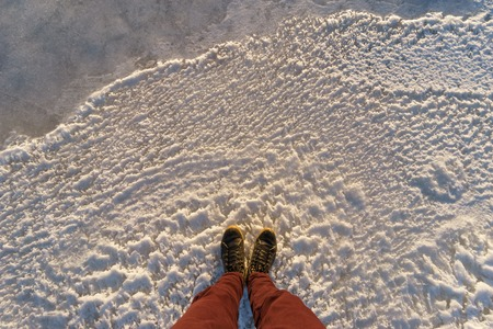 Male legs standing on icy surface, pov shot