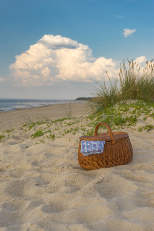 Picnic basket against scenic beach and clouds, weekend break concept