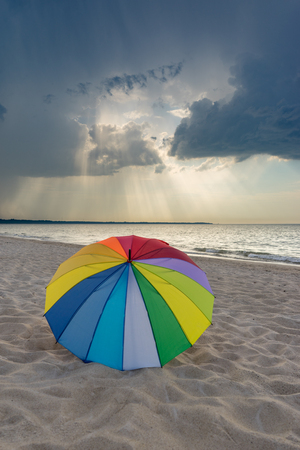 Multicolored umbrella on the beach against dramatic stormy clouds Reklamní fotografie