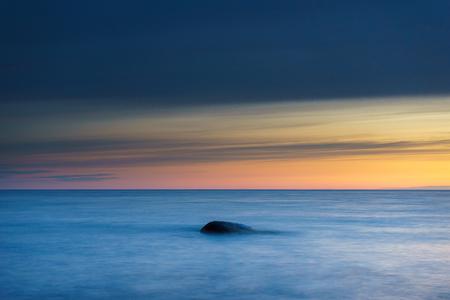 Stone in sea waves against colorful morning sky, long exposure shot Reklamní fotografie