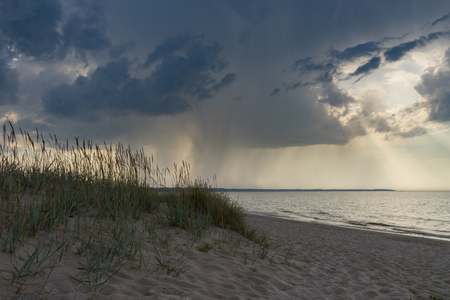 Wild sandy beach against sea and dramatic stormy clouds