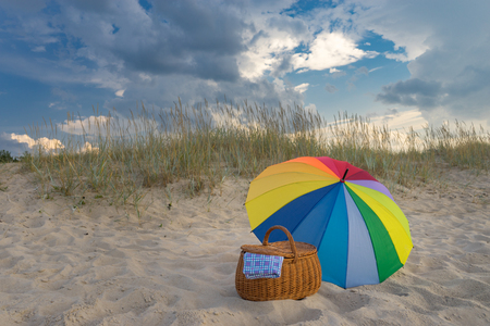 Multicolored umbrella and picnic basket against wild beach and clouds, weekend break concept