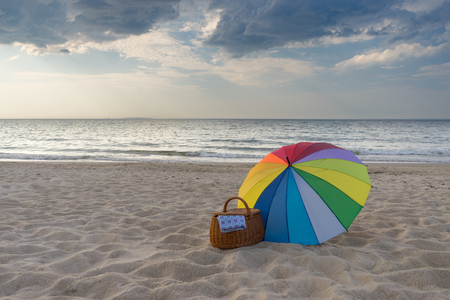 Multicolored umbrella and picnic basket against scenic beach and sea, weekend break concept Reklamní fotografie