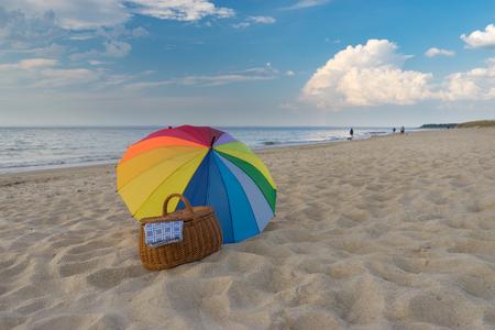 Multicolored umbrella and picnic basket against scenic seacoast, weekend break concept