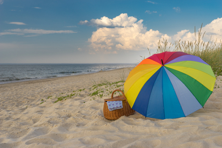Multicolored umbrella and picnic basket against scenic beach and clouds, weekend break concept