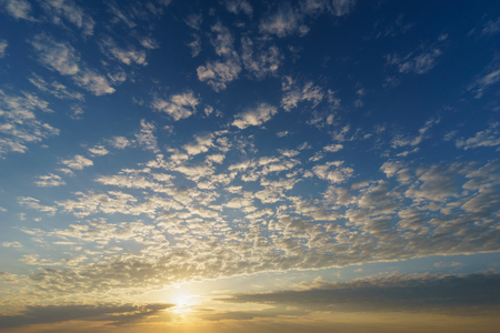 Rising sun over blue sky with cirrocumulus clouds, natural background Reklamní fotografie