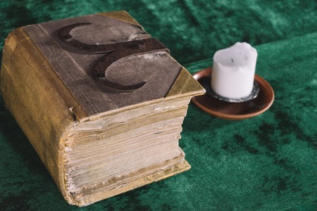 Old heavy book and candle on the medieval table, diagonal view