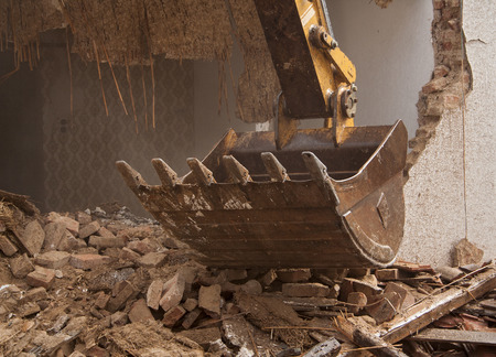 dismantling: A large track hoe excavator tearing down an old house