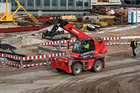 construction vehicle: Red Telescopic handlers deployed on a large construction site Editorial